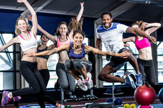 Fit group smiling and jumping