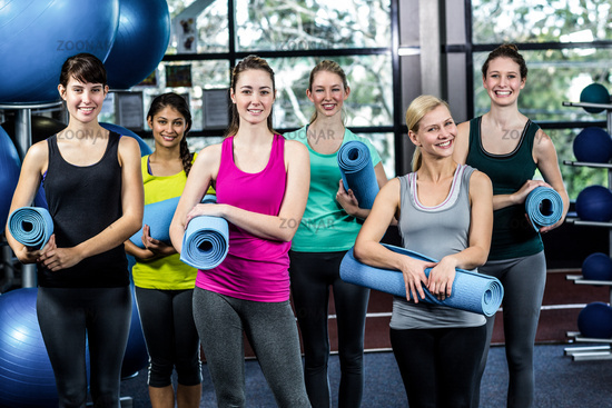 Fit smiling group holding sports mats