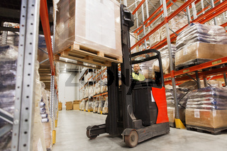 man on forklift loading cargo at warehouse