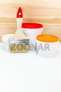 paint cans with brush against wooden background