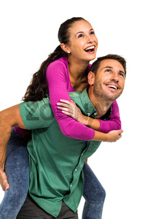 Smiling man giving piggy back to his girlfriend