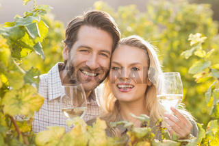 Young happy couple holding glasses of wine