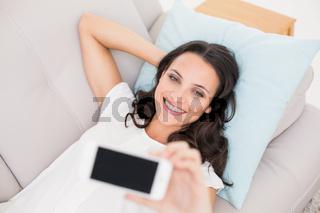 Pretty brunette taking a selfie on couch