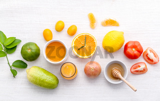 Breakfast with orange juice, oranges, oranges slice, passion fruit , ginger,tomato and Kiwi set up on wooden table .
