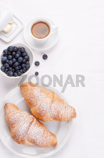 Couple of croissants on a white plate with coffee and blueberries. selective focus. top view