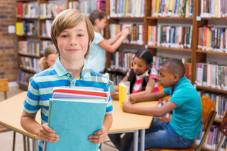Cute pupil smiling at camera in library