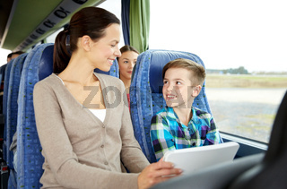 happy family with tablet pc sitting in travel bus