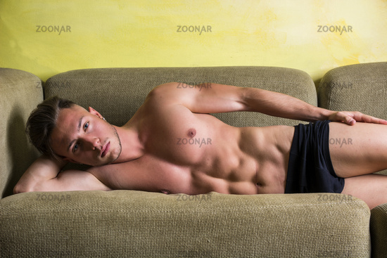 Shirtless muscular young man at home on couch