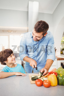 Man smiling while chopping vegetable with son