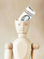Bundle of dollars into the human head. Abstract image with wooden puppet