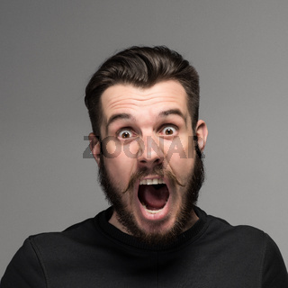 Portrait of a young surprised businessman with opened mouth