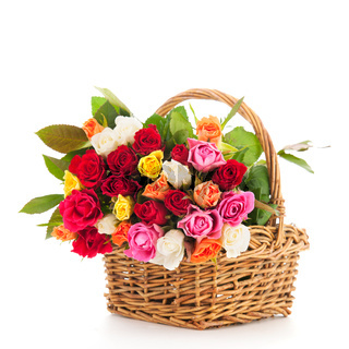 Colorful bouquet mixed roses in wicker basket