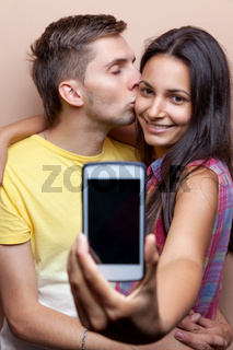 Young happy couple taking a selfie with mobile phone