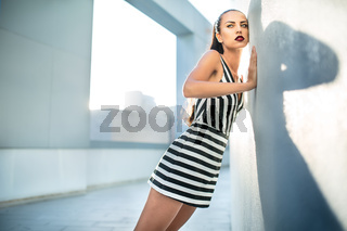 Fashion model in a striped dress near the wall