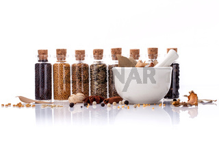 Assorted of spice bottles condiment black pepper ,white pepper, black mustard,white mustard,fenugreek,cumin ,bay leaf ,cinnamon and fennel seeds with mortar isolated on white background.