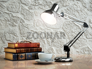 Vintage books coffee cup and desk lamp on the table. Place of work.