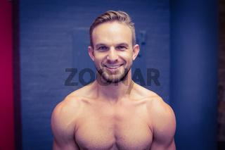 Smiling muscular man looking at the camera