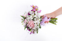 Hand holding a pink, summer bouquet from gillyflowers and alstroemeria on white