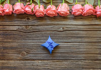 Tiny gift box over wooden background with roses