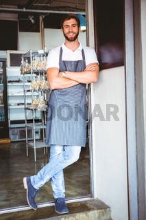 Smiling server in apron arm crossed