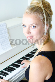 Woman playing with musical notes on a white piano