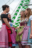 Attractive and joyful woman at German Oktoberfest with traditional dirndl dresses, big wheel in the background.