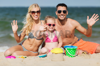 happy family with sand toys waving hands on beach