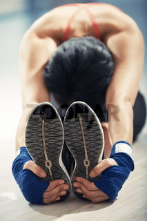 Stretching woman in exercising room