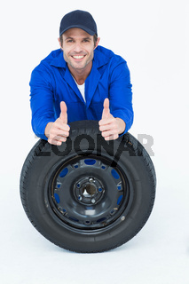 Mechanic leaning on tire while gesturing thumbs up