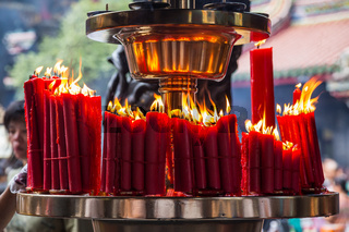 Candles burn in Longshan Buddhist temple in Taipei city Taiwan