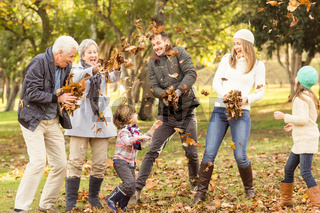 Happy extended family throwing leaves around