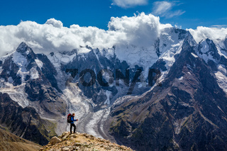 Hiker with backpack standing on mountain top and enjoying scene