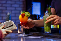 Barmen Serving Cocktails While Woman Waits to Pay