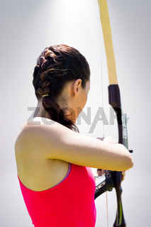 Composite image of rear view of sportswoman doing archery on a white background