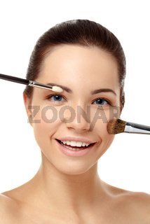 Beauty portrait of pretty girl with brush for makeup