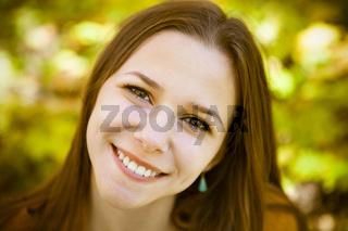 Portrait of a beautiful teenage girl having fun in autumn park