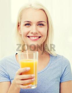 smiling woman drinking orange juice at home