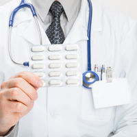 Doctor holdling pills in hand - studio shot