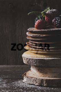 Breakfast in the wood : chocolate pancakes with strawberries, blackberries