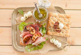 Sandwich mit rohem Schinken und gegrillten Pfirsichen
