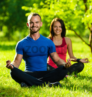 Young man and woman doing yoga in the sunny summer park