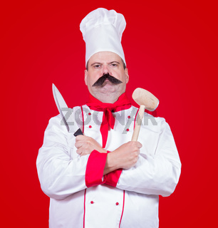 strict cook holding knife and beater
