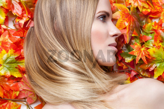 Beautiful young woman lying on autumn leafs
