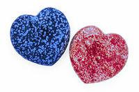 Zwei Herzsteine (Handschmeichler) in Blau und Rot, zueinander geneigt