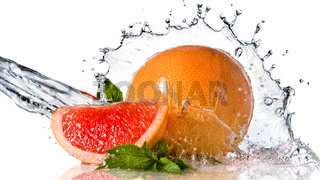 Water splash on grapefruit with mint isolated