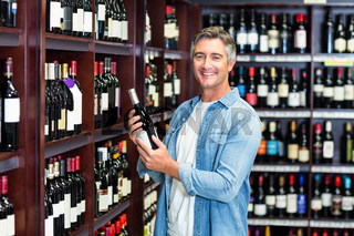 Smiling man holding bottle of wine