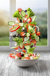 flying salad on wood against window