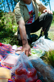 Young man preparing picnic with vegetables bread and ham in the woods