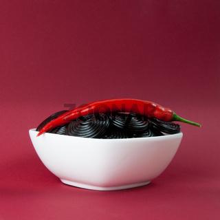 Schale mit Lakritzschnecken und roter Chili