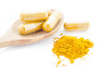 Turmeric powder and a wooden spoon with herbal capsule.